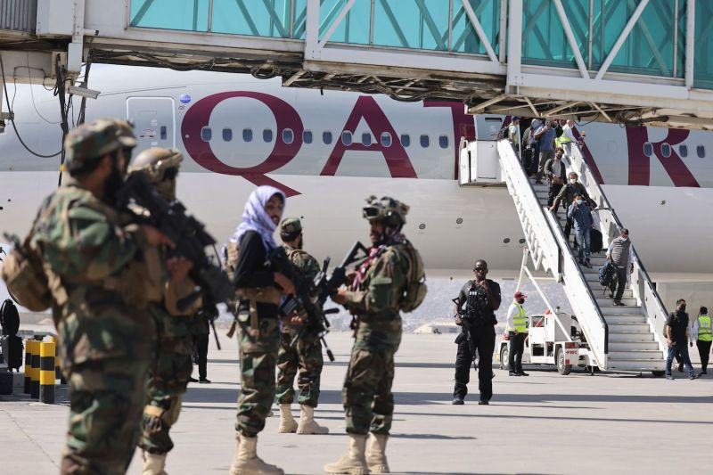 Taliban fighters stand guard as passengers board a plane.