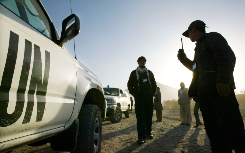 Afghan security officers stand in front of a U.N. vehicle.