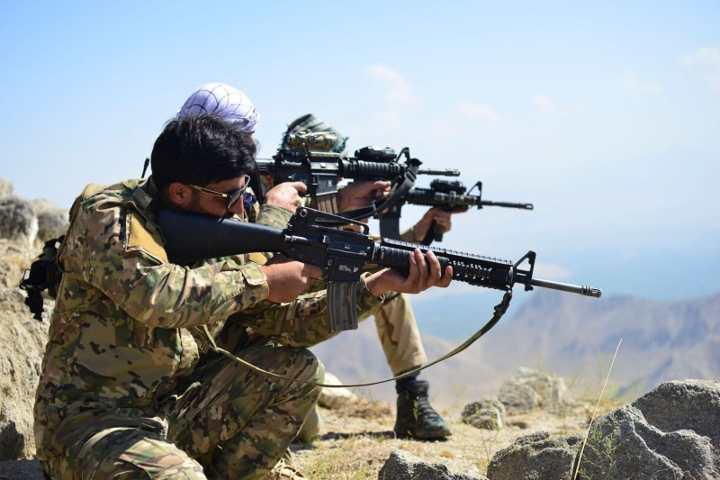 Afghan resistance movement and anti-Taliban uprising forces take positions as they patrol on a hilltop.