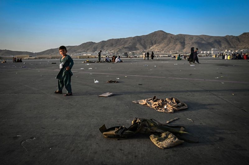 An Afghan child walks near abandoned military uniforms in Kabul.