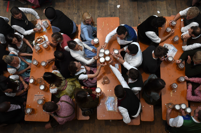 People drink in a festival tent of the Oktoberfest beer festival in Munich, southern Germany, on October 3, 2019.