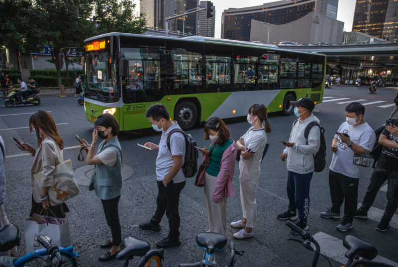 Commuters wait in line for public buses.