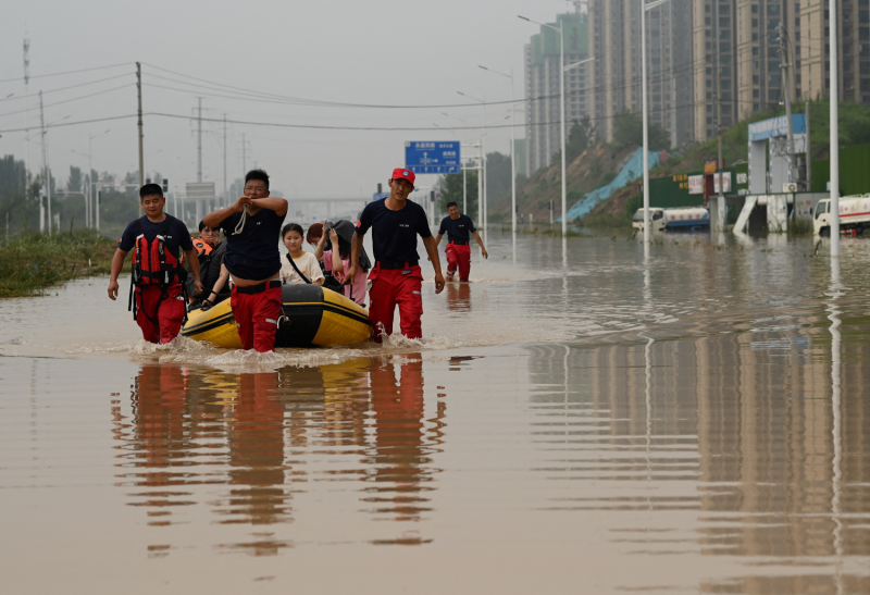 Rescue workers help people cross a flooded street in China.