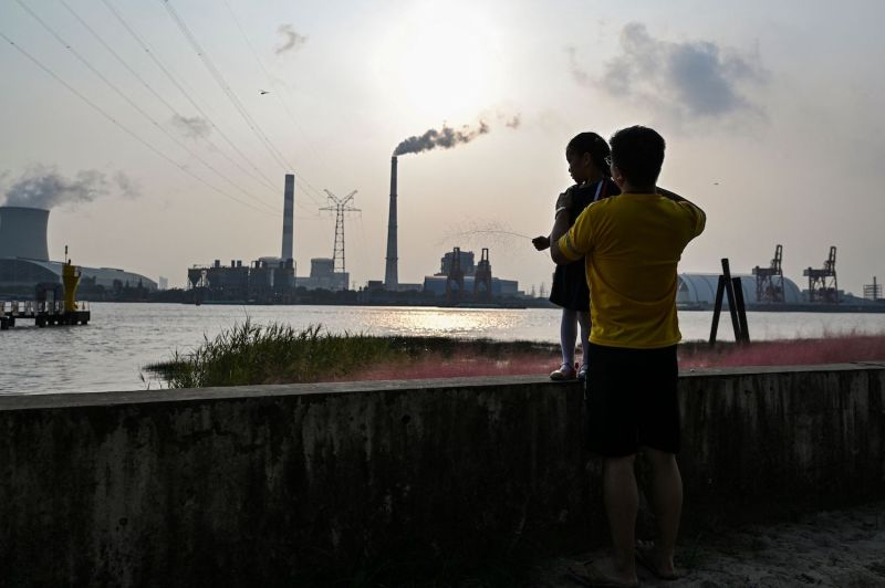 A man holds his daughter across from a coal power station in Shanghai.