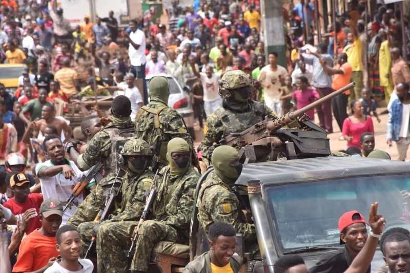 People celebrate in the streets with members of Guinea's armed forces