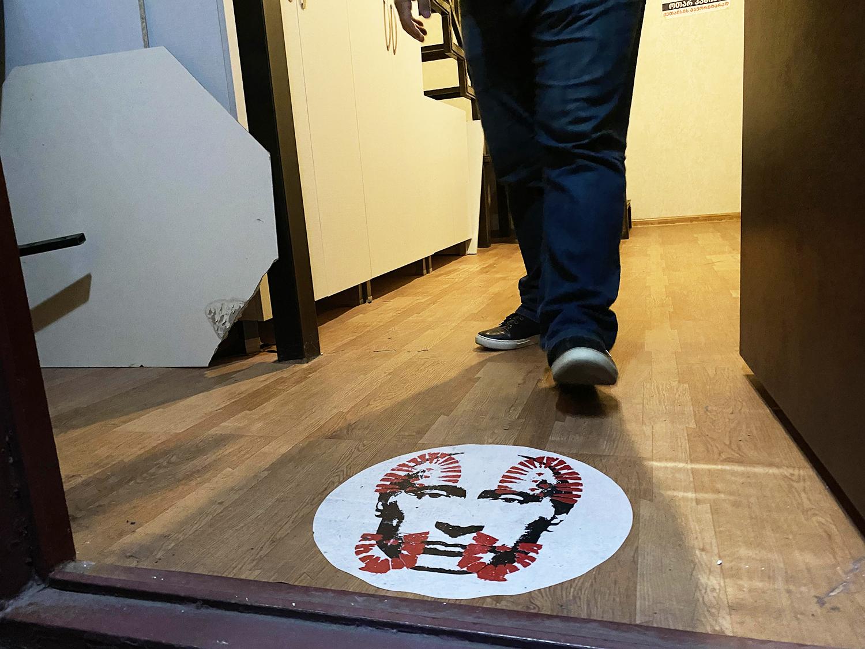 An opposition politician steps on a door sticker.