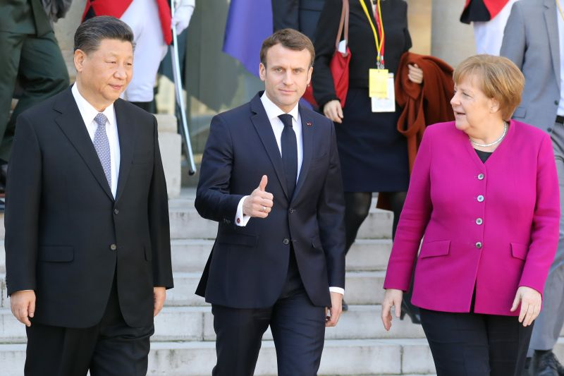 French President Emmanuel Macron gestures next to German Chancellor Angela Merkel and Chinese President Xi Jinping following their meeting at the Elysee Palace in Paris on March 26, 2019.