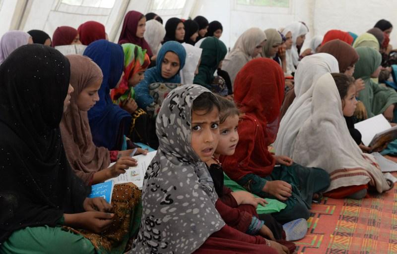 Afghan schoolchildren study at a destroyed high school.