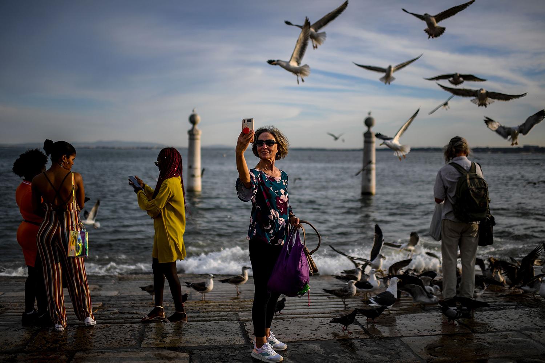 A woman takes selfies at Cais das Colunas in Lisbon.