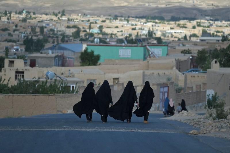 TOPSHOT - Women walk through a road in Ghazni on June 3, 2021.