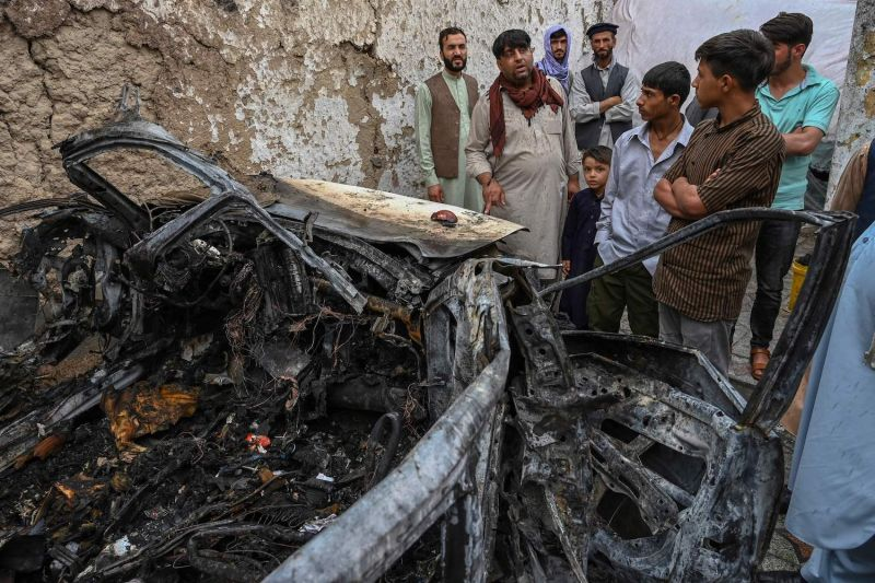 Afghans gather next to a damaged vehicle after a U.S. drone strike in Kabul.