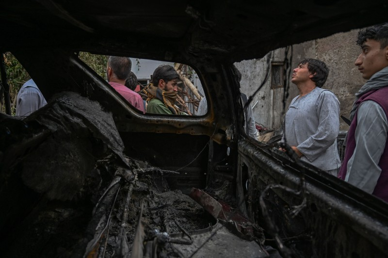 Afghan residents and victims' family members gather next to a vehicle that was damaged in a U.S. drone airstrike the day before in Kabul on Aug. 30.