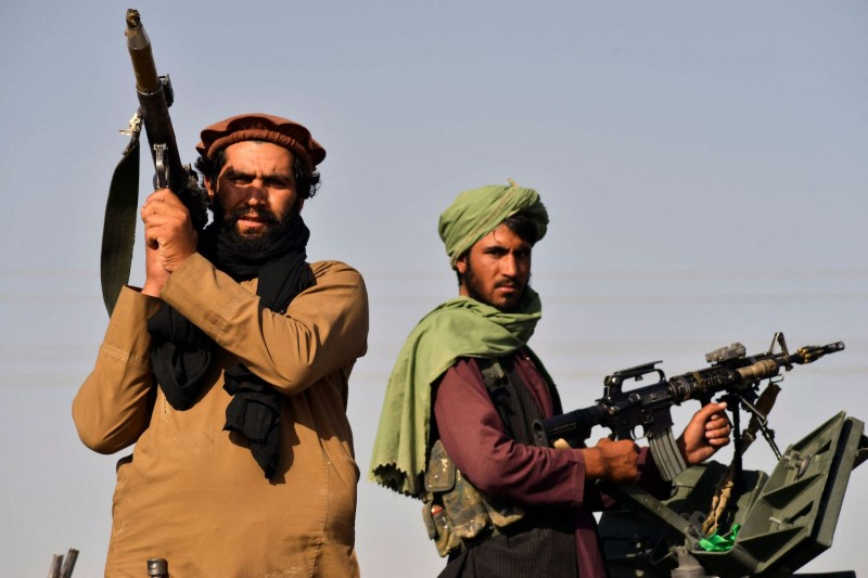 Taliban fighters stand on an armored vehicle.
