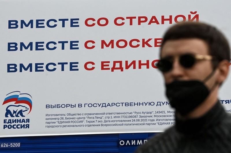 A man walks past a United Russia party campaign poster in Moscow.