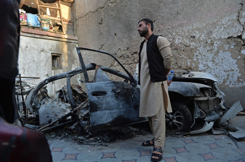 The brother of Ezmarai Ahmadi, a civilian wrongly identified as an Islamic State militant and killed in a U.S. drone strike, stands next to the wreckage of a vehicle that was damaged in the strike in the Kwaja Burga neighborhood of Kabul on Sept. 18.
