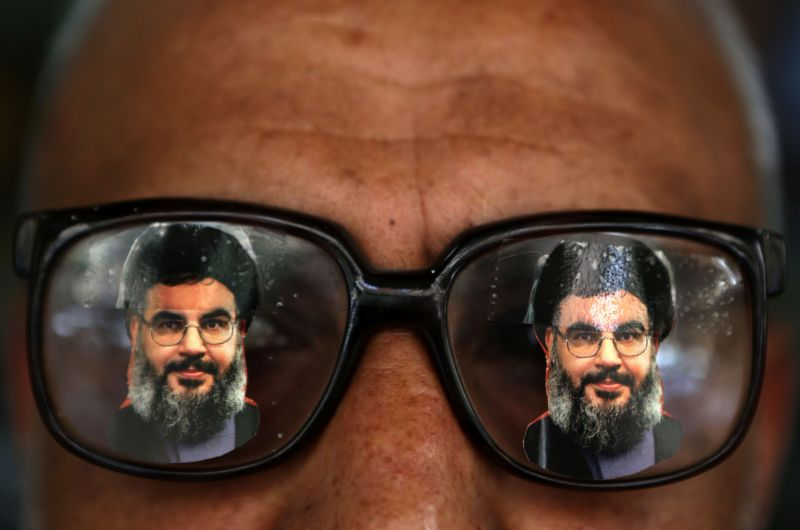 A souvenir shop owner displays glasses decorated with pictures of Hassan Nasrallah.