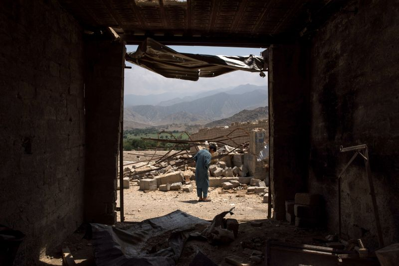A boy walks through buildings damaged from fighting.