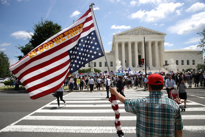 A man bearing an upside-down American flag watches as protesters gather outside the U.S. Supreme Court in Washington, D.C., on June 26, 2018.