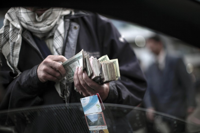 An Afghan street seller offers the local currency called 'afgani' in exchange for US dollars and few pre-paid mobile phone cards, in  Kabul, on April 10, 2010.