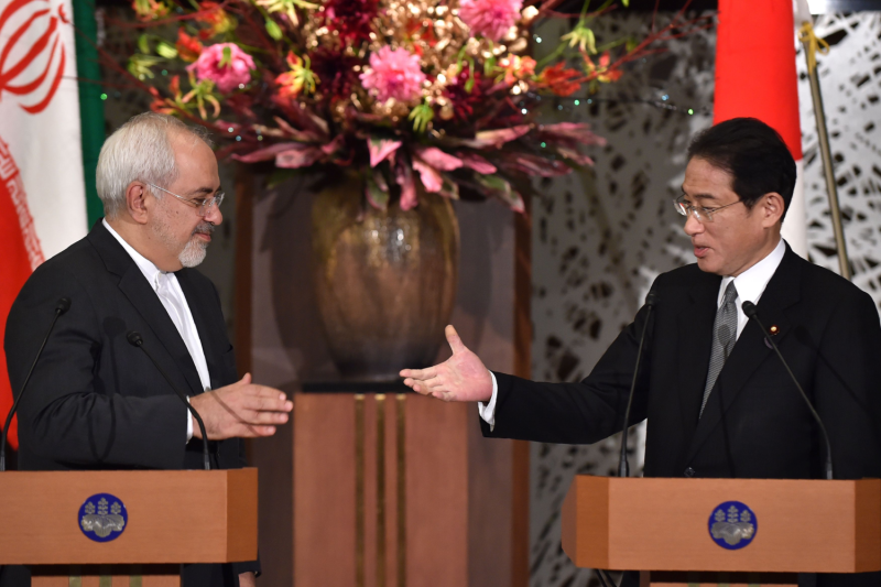The Iranian and Japanese foreign ministers shake hands.