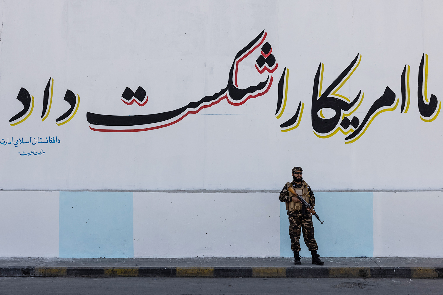 """A solder stands beneath a sign that reads: """"We defeated America"""" near the former U.S. Embassy in Kabul."""