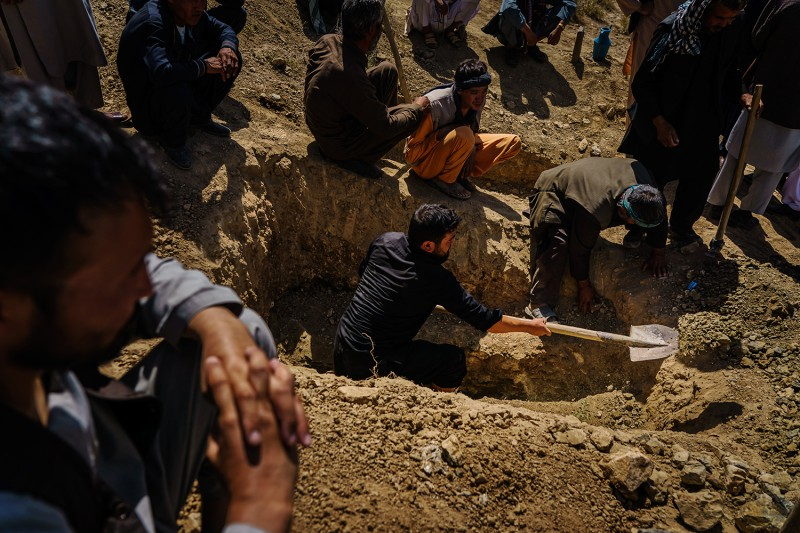 Relatives of a man killed in the Kabul airport bombing bury his body.