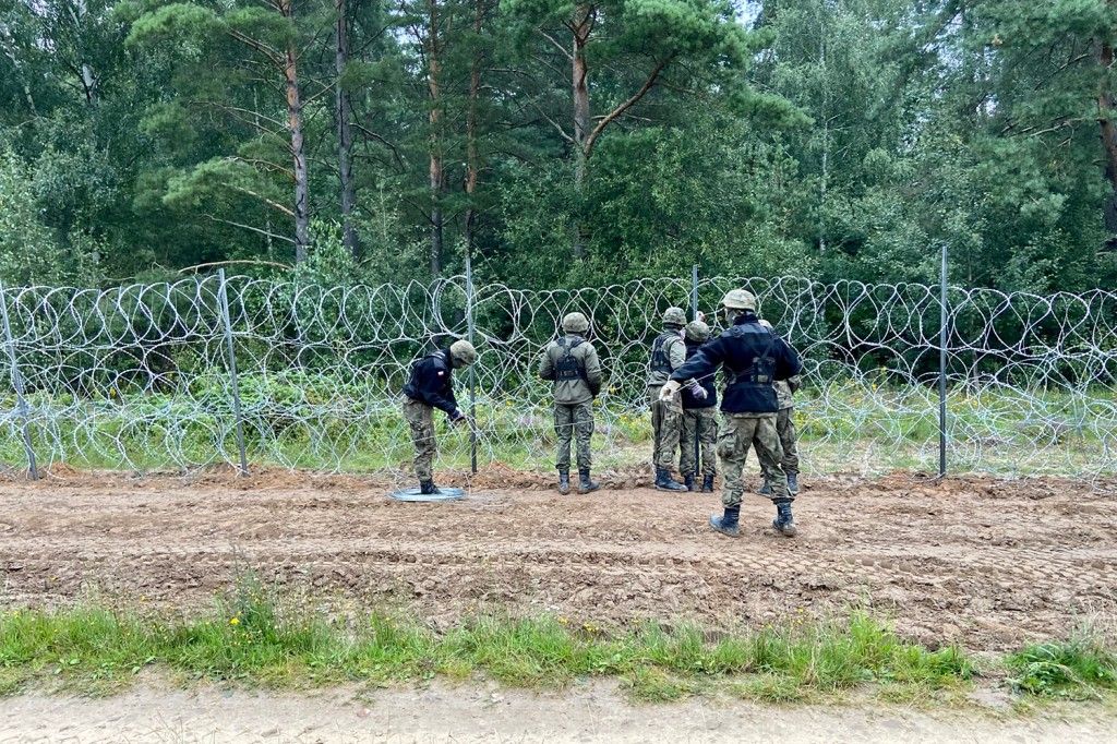Polish soldiers construct a barbed-wire fence on the border with Belarus