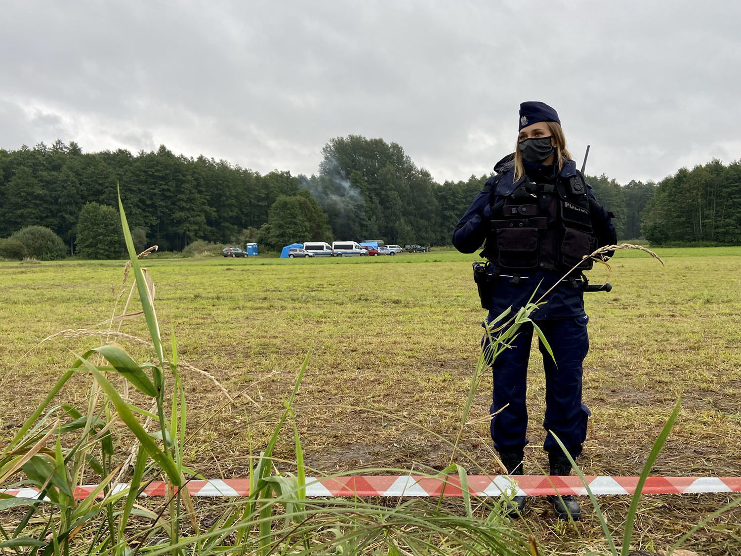 A Polish police officer cordones off the Polish-Belarusian border where the migrants' camp is located in the village of Usnarz Gorny on Aug. 26.