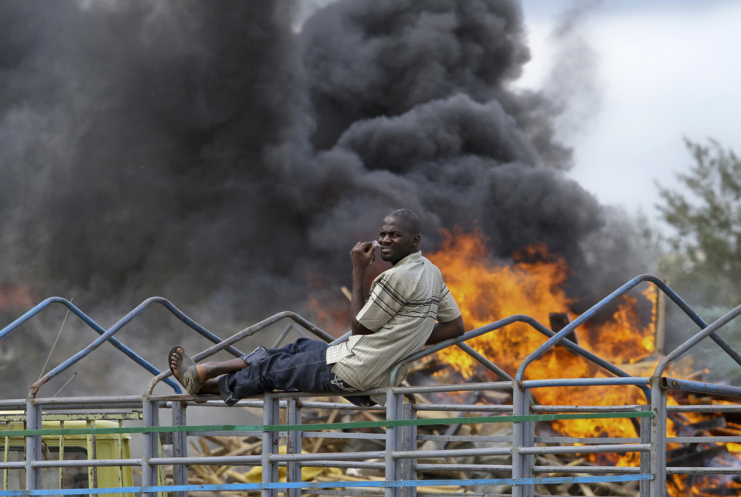 A man sits on top of a truck as smoke rises after the Abuja environmental task force pulled down illegal structures in Utako district in Abuja