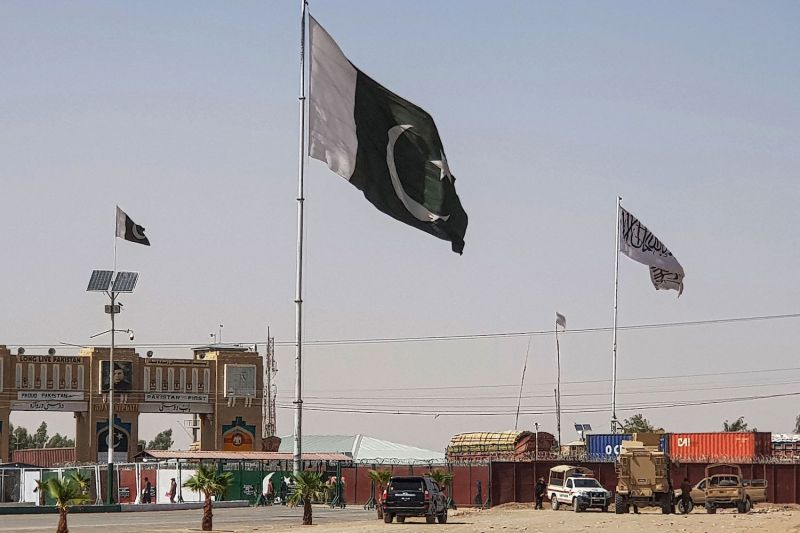 Pakistani and Taliban flags fly on their respective border sides.