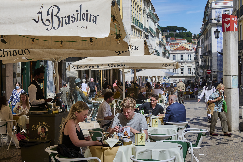 Patrons sit at a sidewalk cafe in Lisbon.