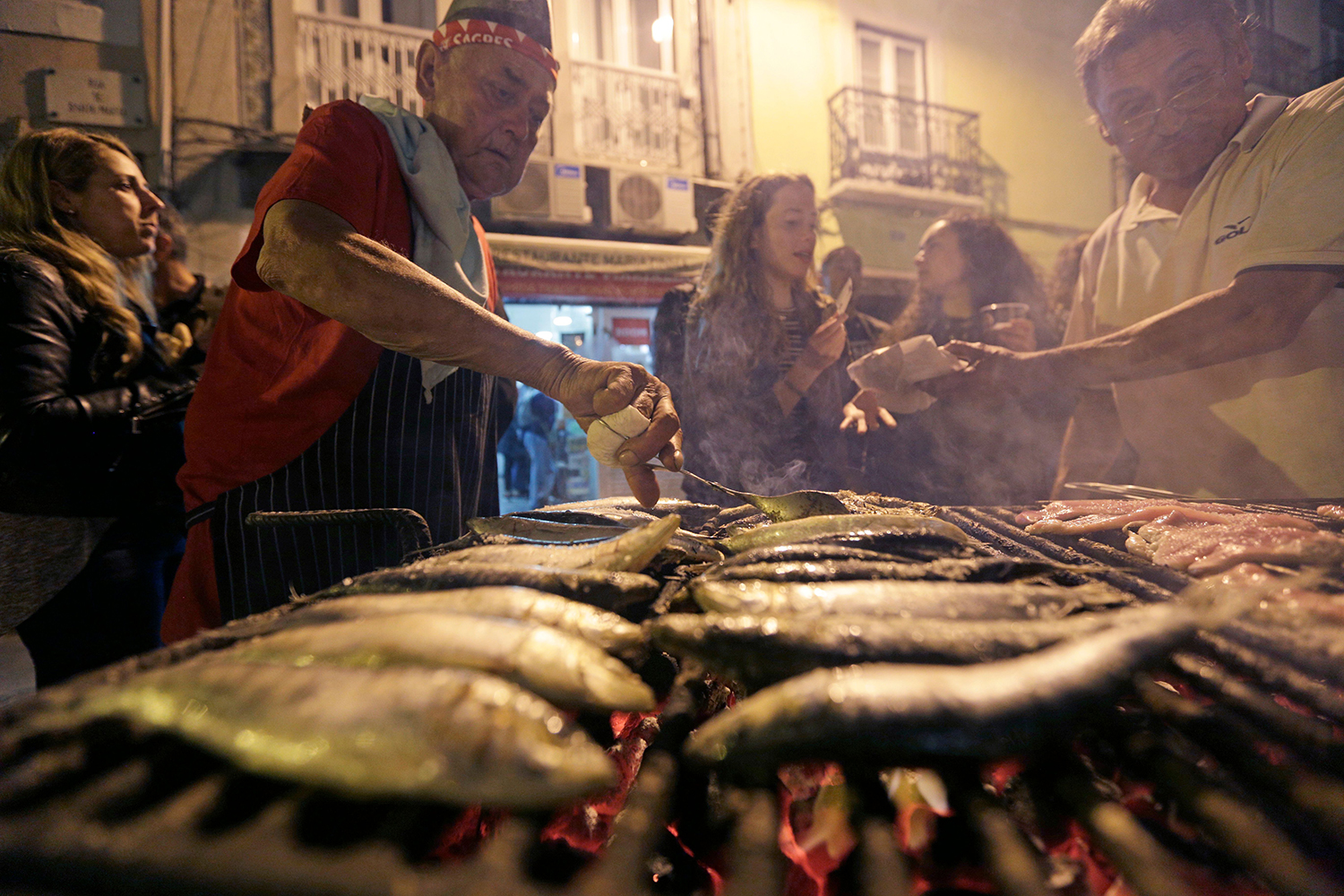 Cooks turn sardines over the grill during the St. Anthony's Day Parade.