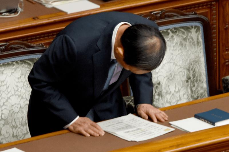 Then-Japanese Chief Cabinet Secretary Yoshihide Suga bows.