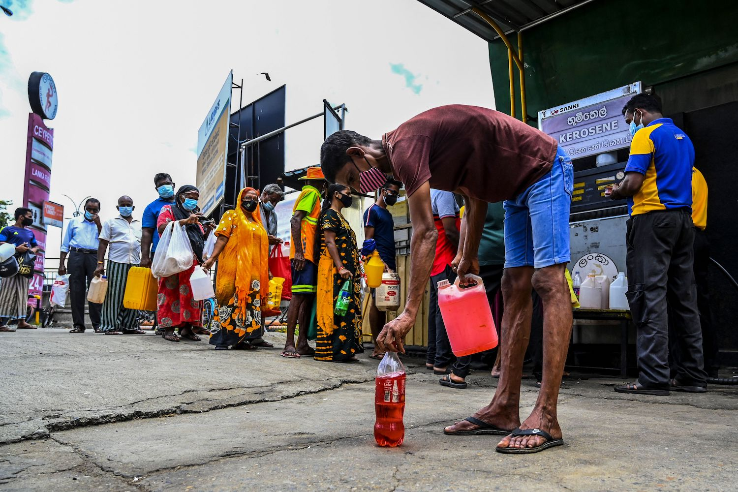 People stand in a queue to buy kerosene oil used in cooking stoves in Colombo, Sri Lanka.