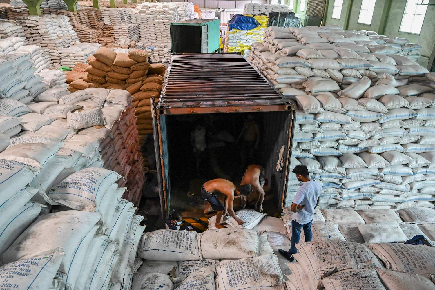 Workers load sugar into a container truck at a private warehouse in Sri Lanka.