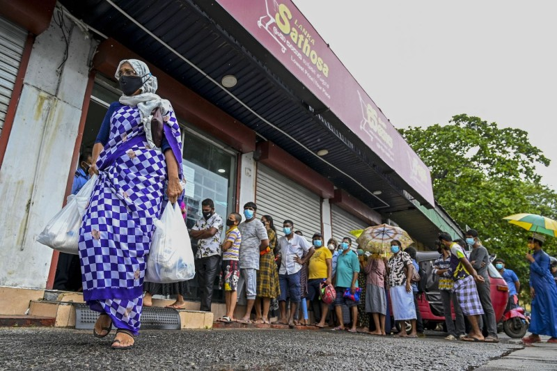 A woman carrying food bags walks pasts people queuing outside a state-run supermarket in Sri Lanka.