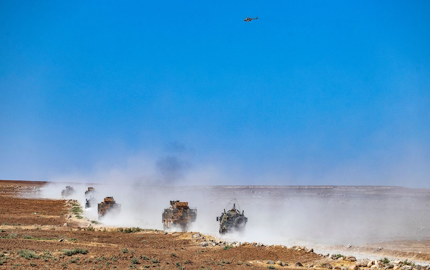 A Russian helicopter hovers as Turkish and Russian military vehicles patrol in Syria.