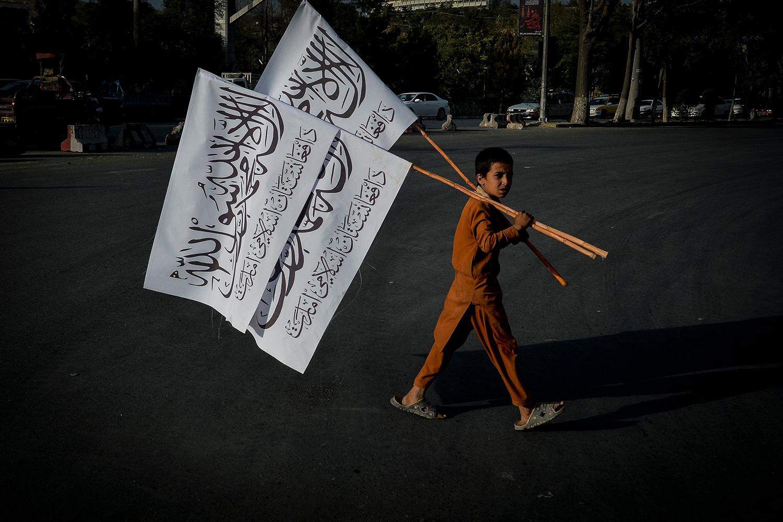 A boy carries Taliban flags.