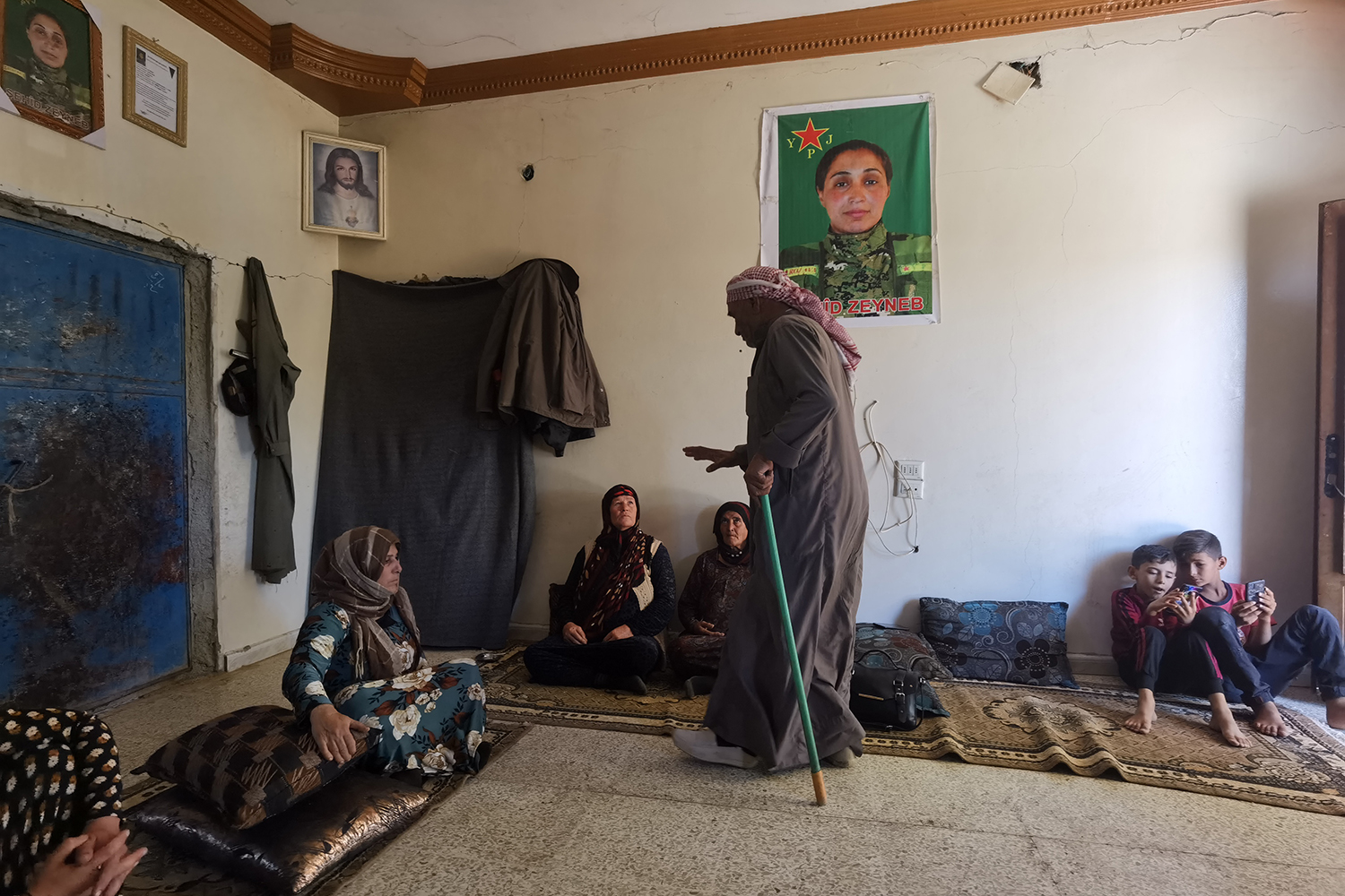 """Serekaniye's mother and other family members sit at home in Tal Tamr on Sept. 4 under a framed image of Serekaniye, who the YPJ has honored as a """"sehid,"""" or martyr."""