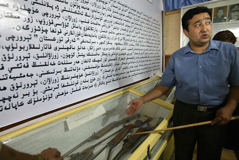A CCP official gestures at ETIM weapons.