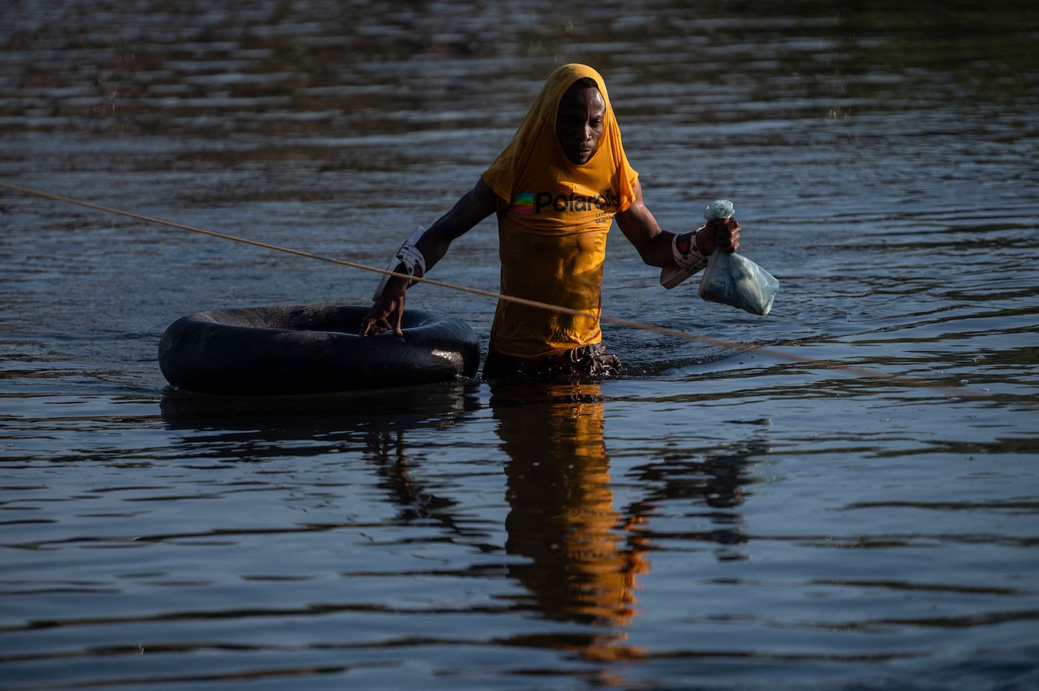 A Haitian migrant crosses the Rio Grande to get food and water in Mexico.