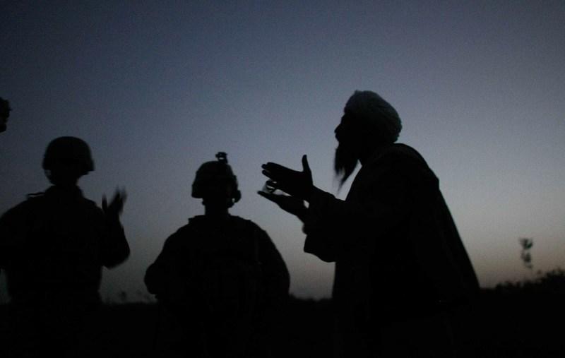 Members of the U.S. Marines speak to an Afghan man.