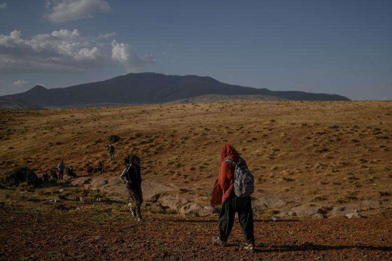 Afghan migrants wait for transport.