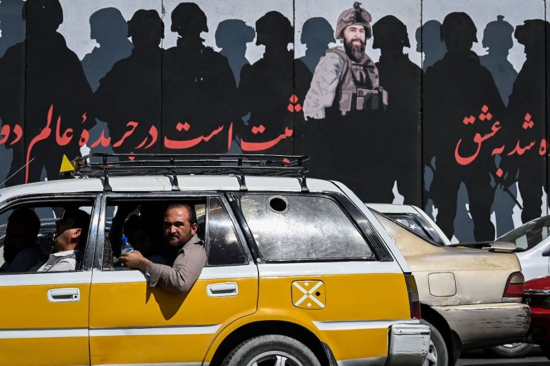 A man looks out of a car window as commuters make their way along a road in Kabul on Sept. 5.