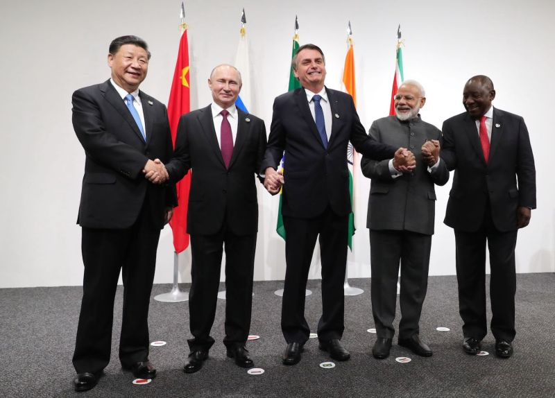 Chinese President Xi Jinping, Russian President Vladimir Putin, Brazilian President Jair Bolsonaro, Indian Prime Minister Narendra Modi, and South African President Cyril Ramaphosa link hands as they pose in front of their countries' flags.
