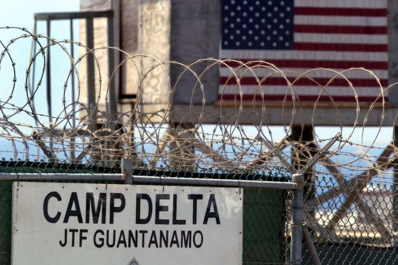 """A sign on a fence topped with razor wire reads """"Camp Delta JTF Guantanamo."""""""