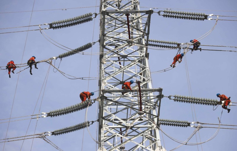 Electrical workers carry out maintenance work on a transmission tower in Qingdao, China, on Sept. 24.