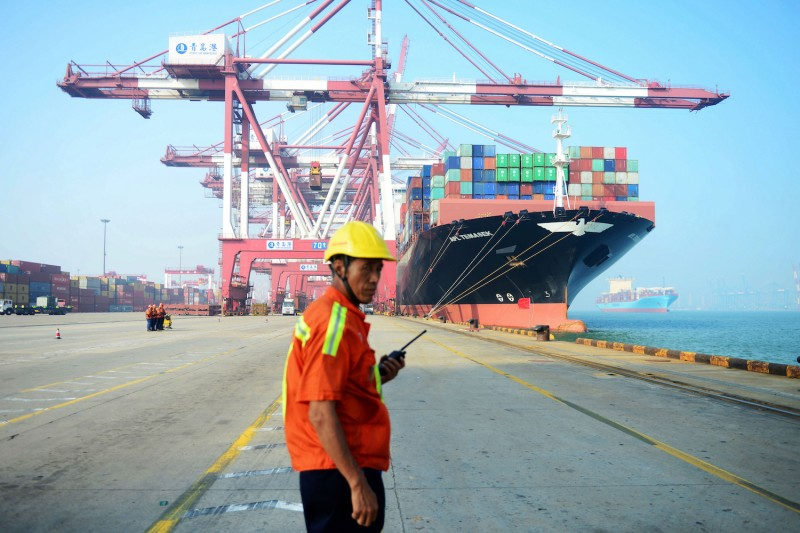 A Chinese worker in a yellow hardhat looks on as a cargo ship is loaded with shipping containers at a port.