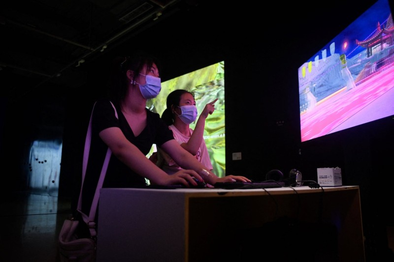 Two girls play video games at a digital art exhibition at a museum in Beijing on Aug. 12.