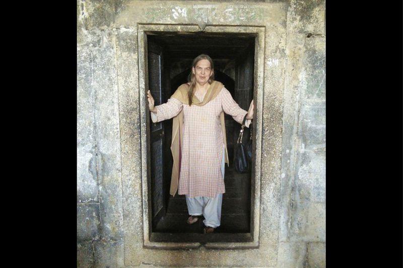 Gail Omvedt stands in a doorway
